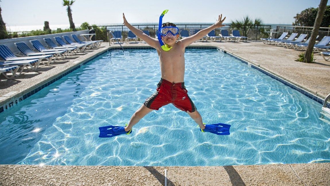 Boy jumping at the Captain's Quarters hotel pool