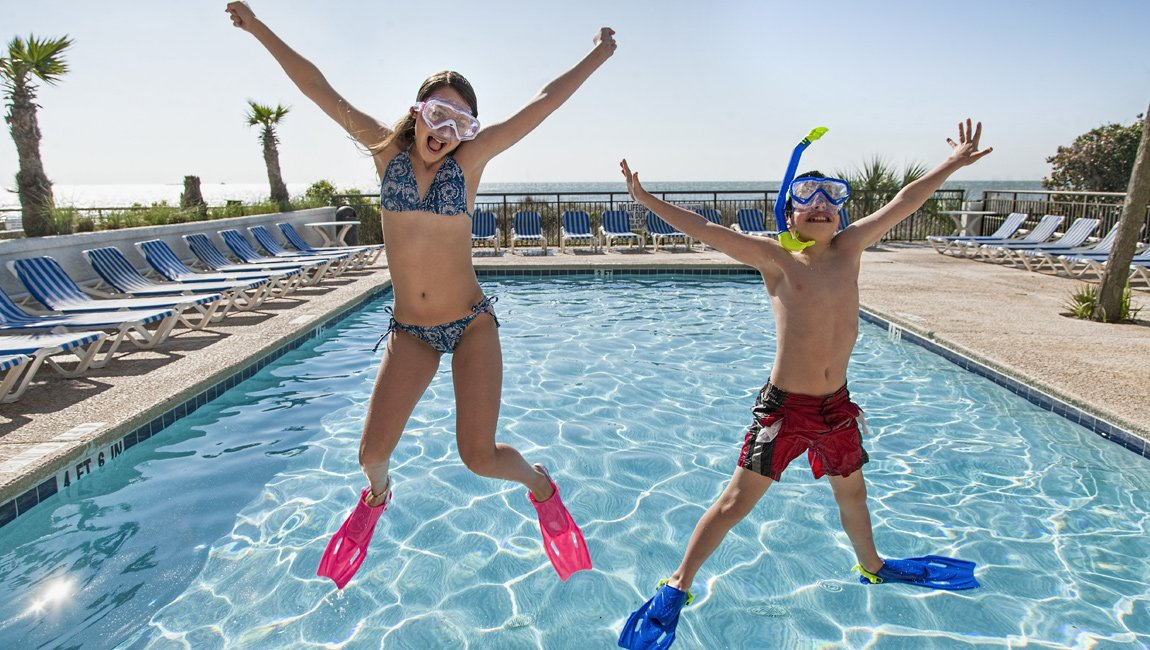 Siblings jumping at the outdoor resort Myrtle Beach pool