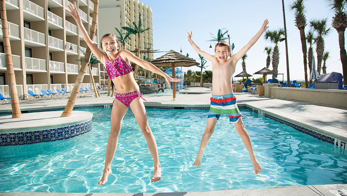 Kids Jumping At Outdoor Pool