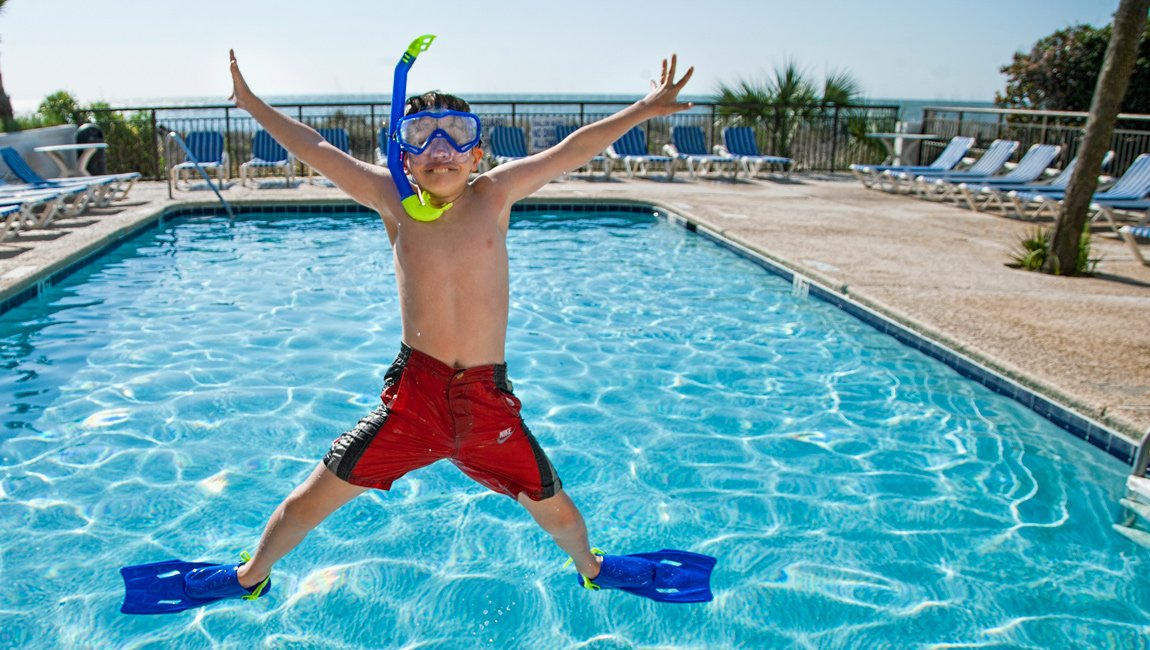 Boy jumping by the outdoor pool